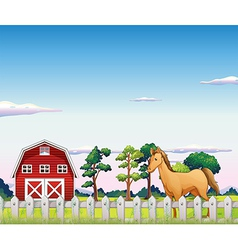 A horse inside the fence with a barn vector image vector image