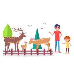Child with parent at zoo near deers family corral vector
