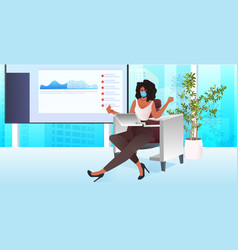 Businesswoman in mask sitting at workplace vector