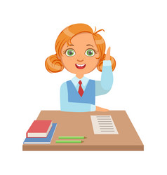 cute schoolgirl sitting at the desk and raising vector image
