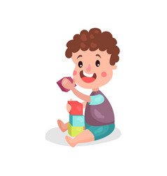 adorable little boy sitting on the floor playing vector image