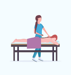 Young girl having hot stone back massage masseuse vector