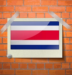 Flags Costa Rica scotch taped to a red brick wall vector image