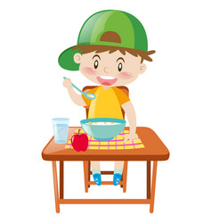 Little boy at dining table eating breakfast vector