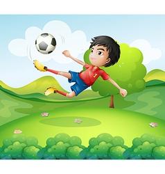 A boy kicking soccer ball at hilltop vector