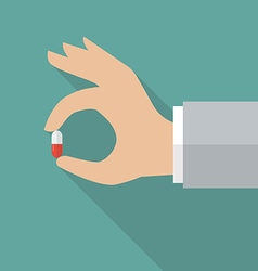 Hand holding medical pill vector