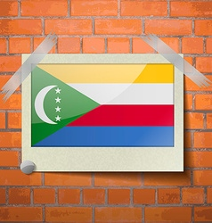 Flags Comoros scotch taped to a red brick wall vector