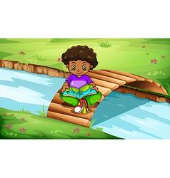 A boy reading at the bridge vector image