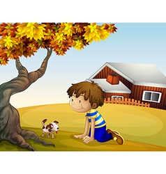 A boy and his puppy under the tree vector image vector image