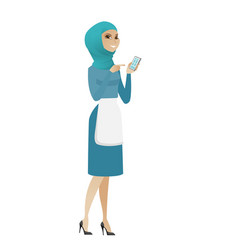 Young muslim cleaner holding a mobile phone vector
