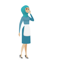 Young muslim cleaner talking on a mobile phone vector