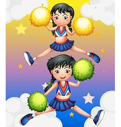 Two cheerdancers dancing with their pom poms vector