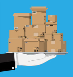 pile cardboard boxes in tray in hand vector image