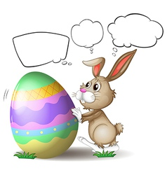 A rabbit pushing a colorful egg vector image vector image