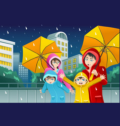 Family walking with umbrella and wearing raincoats vector