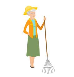 Senior caucasian farmer holding gardening rake vector