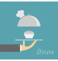 Hand holding silver platter cloche with chefs hat vector image