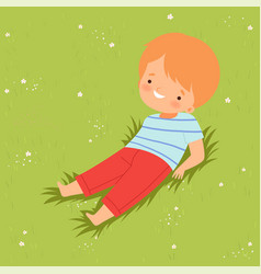 Smiling boy lying down on green lawn cute kid vector