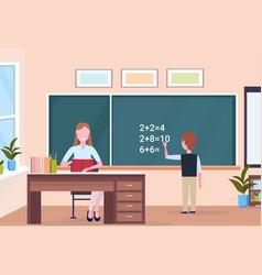 woman teacher sitting at desk schoolboy solving vector image