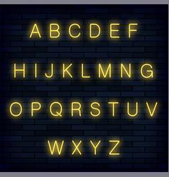 yellow neon alphabet on blue brick background vector image