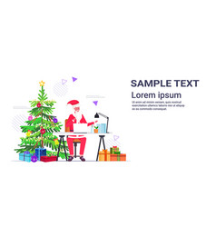 santa claus using laptop sitting at workplace near vector image