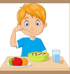 cartoon little boy having breakfast cereals vector image