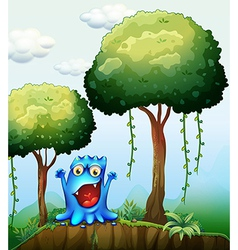 A smiling blue monster at the forest near the vector image