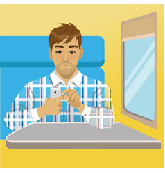 man with smartphone sits near window at train vector image