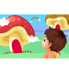 A young boy watching the giant mushroom houses vector