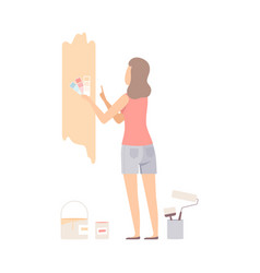 woman picks color for paint wall with swatches vector image