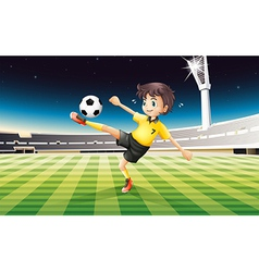 A boy in his yellow uniform playing soccer at the vector image vector image