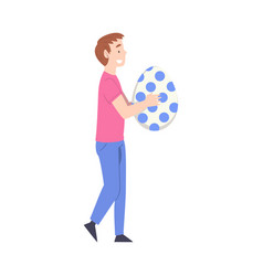 teenage boy carrying huge decorated easter egg vector image