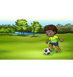 A young boy playing soccer near the river vector