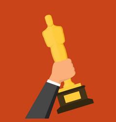 Hand holding golden award statuette over red vector