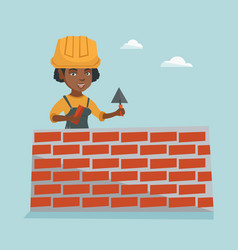 Young african bricklayer building a brick wall vector