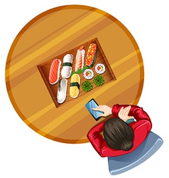 A topview of a girl at the table with sushi vector