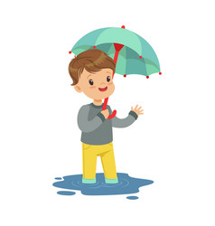 cute little boy standing in the puddle and holding vector image