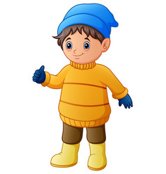 Happy boy in yellow winter clothes giving thumbs u vector