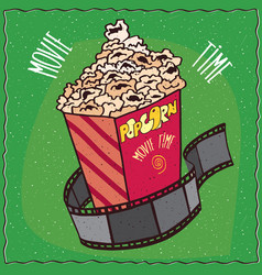 cardboard box with popcorn and reel of film vector image