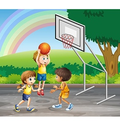 Three children playing basketball at the court vector image vector image