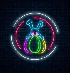 Glowing neon easter bunny with eggs sign in vector