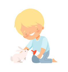 Little boy feeding his fluffy rabbit isolated on vector