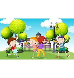Children playing water gun in the park vector image
