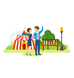 Couple walks past playground and circus eating vector