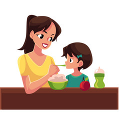 mother spoon feeding her little daughter sitting vector image