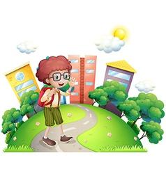 A schoolboy waving while walking at the road vector image vector image
