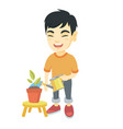asian boy watering plant with a watering can vector image vector image