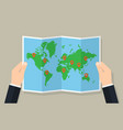 hands hold folded paper map of world with markers vector image vector image