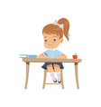 cute girl sitting at the desk and writing vector image vector image