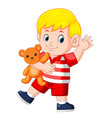 a cute boy play with the orange teddy bear vector image vector image